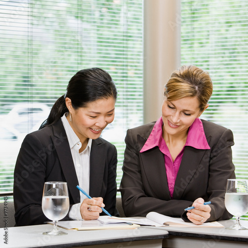 Businesswomen reviewing paperwork in conference room