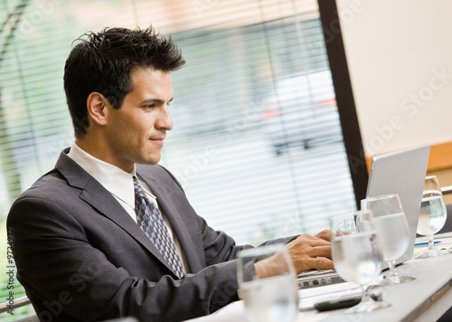 Businessman sitting in conference room working on laptop