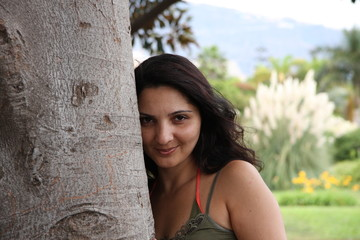 Porträt dunkelhaarige junge Frau lehnt an Baum