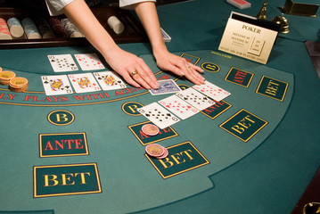 dealer handling playing cards at a poker table in casino