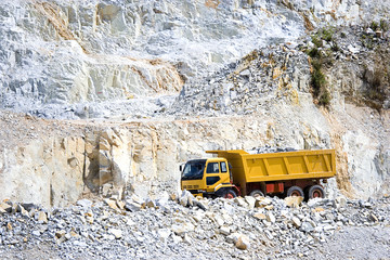 Image of a yellow truck at a rock quarry in Malaysia.