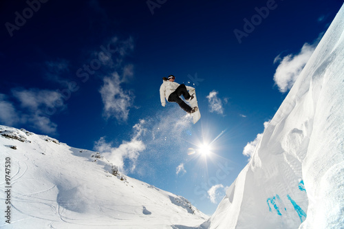 Snowboarder jumping through the air with blue sky background
