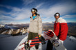 Two snowboarders stand on a peak over looking a spectacular view