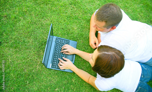 caucasian couple using laptop in park. love and family