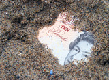 Hole reveals ten pound note buried in sand poster