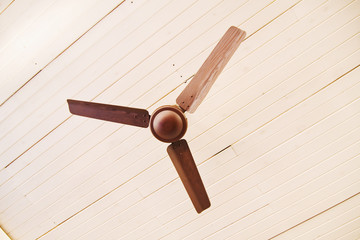 The brown fan against a white ceiling