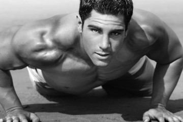 young man with naked torso doing push-ups on the beach