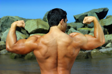 full color photo of body builder flexing his back by the ocean
