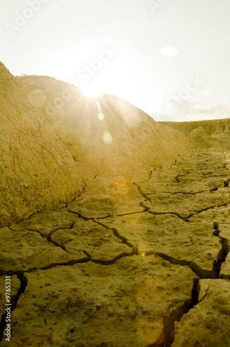 Sun setting over arid land - 9765331
