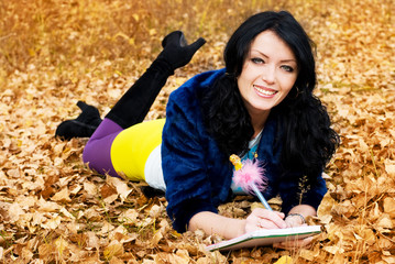 pretty brunette girl in the park with a pen and a note-book