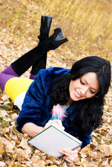 pretty student doing homework in the park