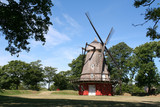 Red windmill surrounded by trees in Copenhagen poster