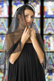 beautiful woman with a black veil on her head like old sicilian