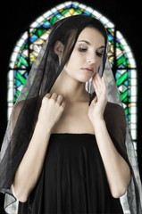 beautiful woman with a black veil on her head in a church