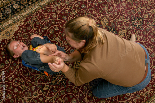 mother tickling her son's bare feet on the carpet