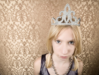 Portrait of pretty pouting young girl wearing a tiara