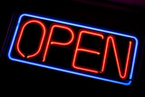 A neon OPEN sign glowing red in the window of a restaurant