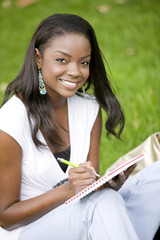 casual female student smiling and holding a notebook
