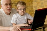 Grandfather and grandson working on laptops poster