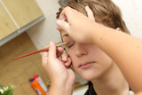 A cosmetologist applies eyeshadow for a woman poster