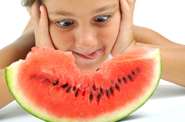 A little girl looking at a slice of watermelon