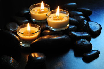Close up of three burning candles and black stones