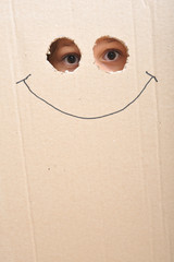 Eyes looking through two holes on a cardboard and a smile