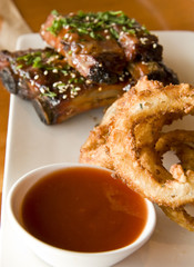 A plate of fried onion rings and barbecued ribs with sauce