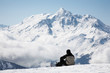 Snowboarder takes a break; French Alps, Europe.