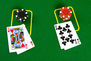Cards and poker chips on green background - top view.