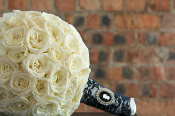 A bridal bouquet of flowers made with cream colored roses