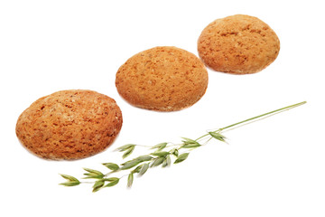 Three oatcakes and green panicle of oat on white background.