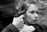 monochrome portrait of man threatens the woman with a pistol poster