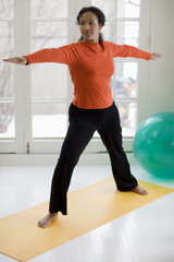 Attractive young black woman in yoga Warrior pose at home