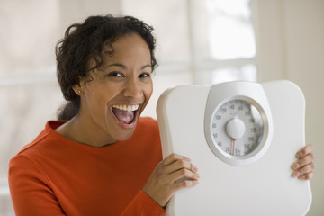 Beautiful young smiling black woman holding scale