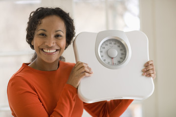 Pretty young smiling Beautiful black woman holding scale