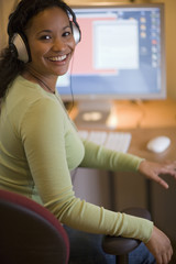 Smiling young black woman with headphones and computer