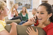 Teenagers Hanging Out In Front Of Television Using Mobile Phones