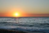 sea beach under glow rays sundown on sky poster