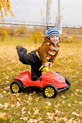 cute little boy playing with his car outdoor