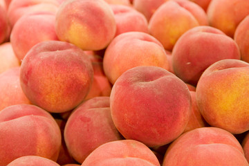 A stack of fresh ripe peaches in a market