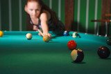 Billiard balls on table, blurred silhouette of cueist