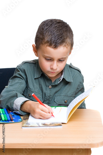 Portrait of a cute schoolboy drawing on a notebook