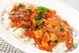 A bowl of chicken curry over steamed white rice.