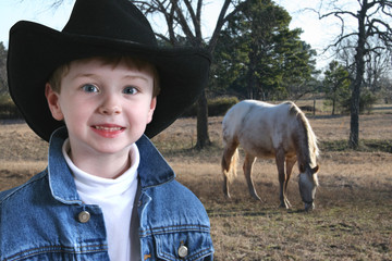 Adorable four year old  in denim jacket and black cowboy hat.