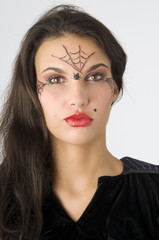 young and nice brunette with spider web painted on face