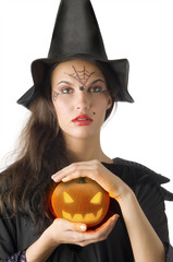 cute girl with witch hat and a little pumpkin betweeen hands
