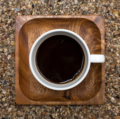 Cup of coffee the top view, on a wooden square plate