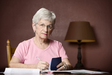 Senior woman with many bills and notices