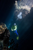 a pretty female scuba diver in a cave with sunbeams poster